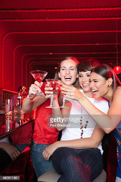Three women with beverages in nightclub toasting and smiling