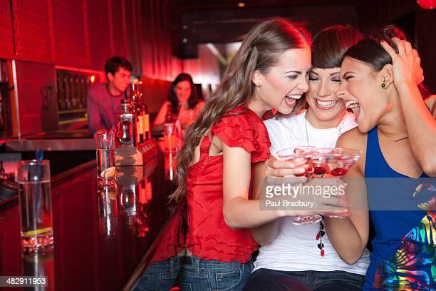 Trois femmes avec des boissons dans la discothèque un toast et souriant