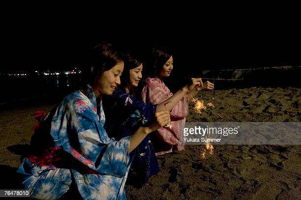 Three women with sparklers by the beach at night