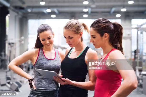 Three women with tablet after exercising in gym