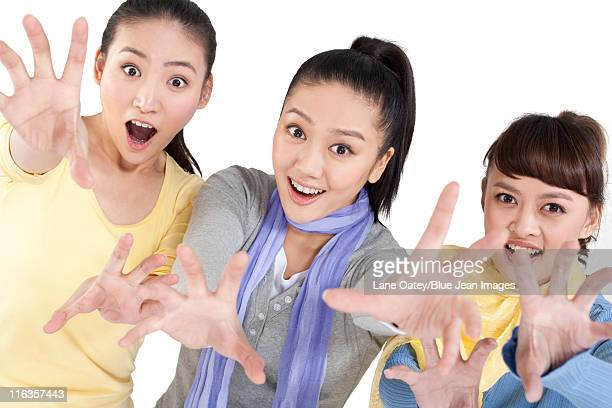 Three women with their arms extended towards the camera