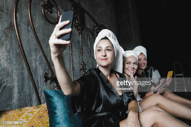 three women with towels around her heads on bed taking a selfie - petite amie photos et images de collection