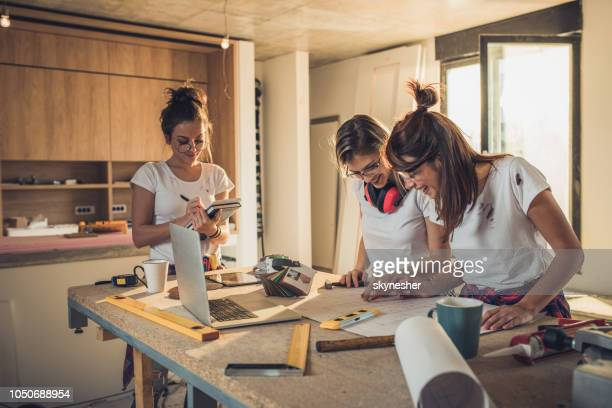 Three women working on housing plan at construction site.