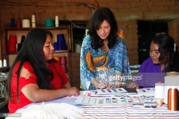 three women working together, looking at a color card on a table of textiles - creative director stock pictures, royalty-free photos & images
