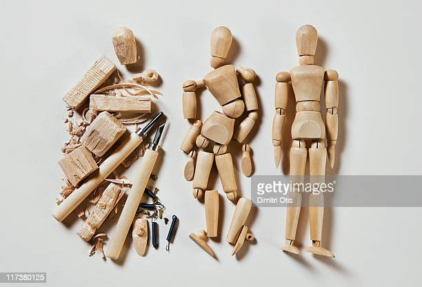 Three wood mannequins in stages of production