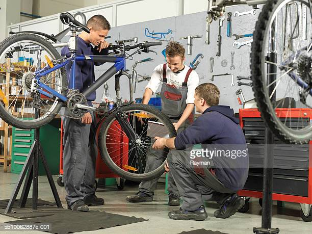 Three workers at a bicycle garage, working on bike, side view