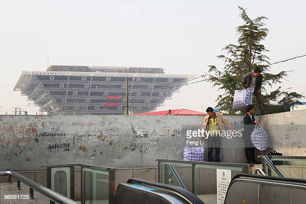 Three workers climb over the wall in front of the construction of the China Pavilion at the World Expo site on April 21 2009 in Shanghai China Expo...