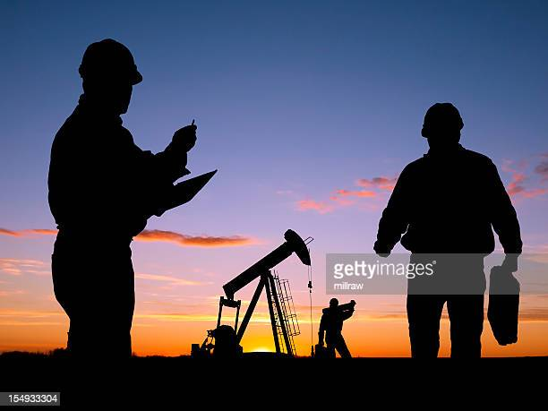 Three Workers Doing Business At Oil Well Pumpjack