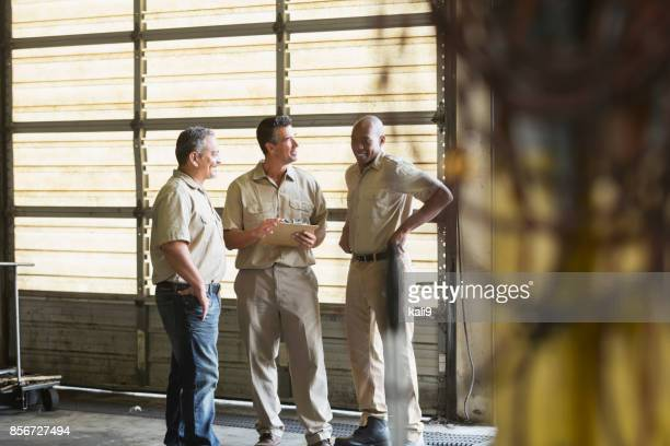 three workers for trucking company having meeting - roller shutter stock pictures, royalty-free photos & images
