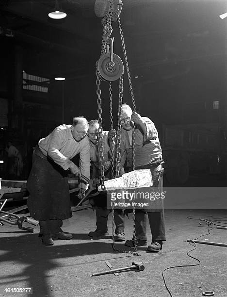 Three workers from Edgar Allen's handle a red hot billet, Sheffield, South Yorkshire, 1963.