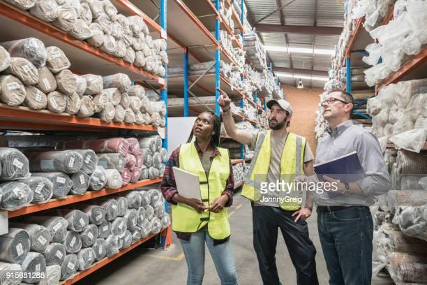 Tres trabajadores en alfombra instalación de almacenamiento