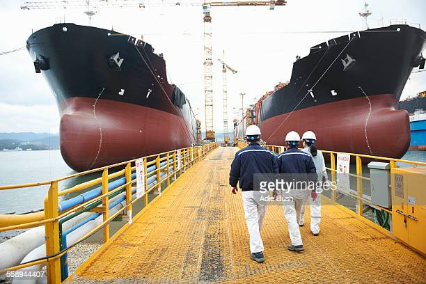 Three workers walking towards ships at shipping port, rear view, GoSeong-gun, South Korea