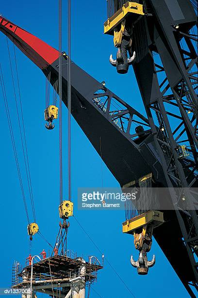 Three Workmen Standing on An offshore Oil Rig Platform By Some Big Cranes