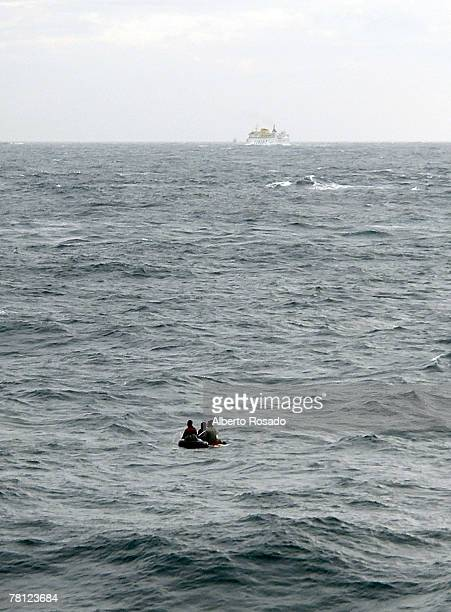 Three wouldbe immigrants from Morocco paddle in rough seas on a windsurf board trying to cross the Strait of Gibraltar moments before being resqued...