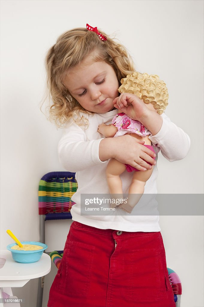 three year old blonde girl holding her baby doll stock photo getty images. Black Bedroom Furniture Sets. Home Design Ideas