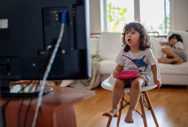 Three year old boy eating in front of a television and surprised from what he see