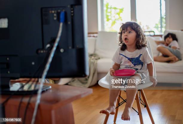 three year old boy eating in front of a television and surprised from what he see - film stock pictures, royalty-free photos & images