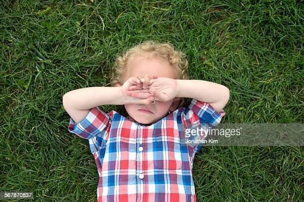 Three year old boy laying on grass