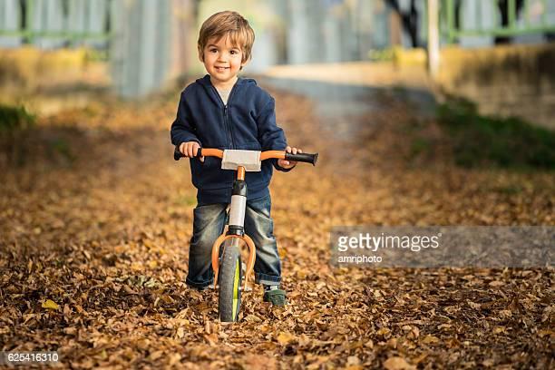 three year old boy on his balance bike smiling