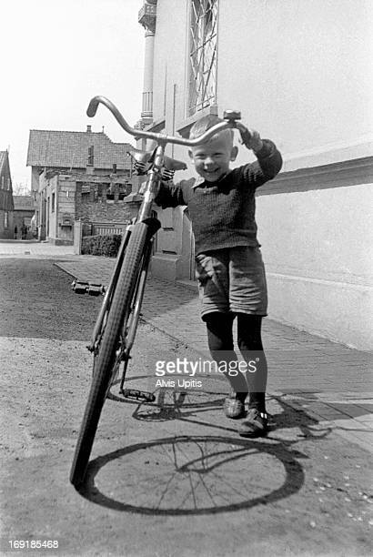 Three year old boy pushes adult bicycle.