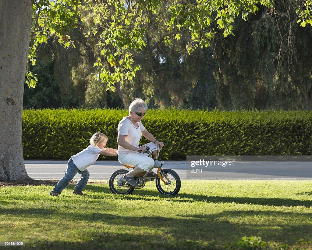 Three year old boy pushing grandmother on cycle in park : Stock Photo