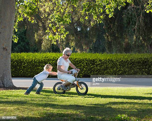 Three year old boy pushing grandmother on cycle in park