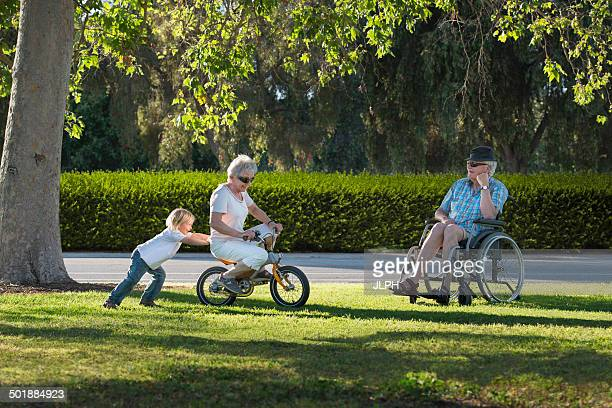 Three year old boy pushing grandmother on cycle with grandfather watching from wheelchair