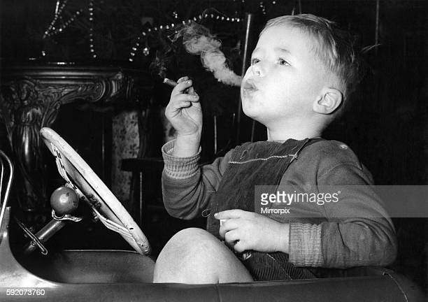 Three year old David Fellows puffs away happily in his pedalcar on a mansized cigar Mr Fellows who has four other children allows David to smoke...