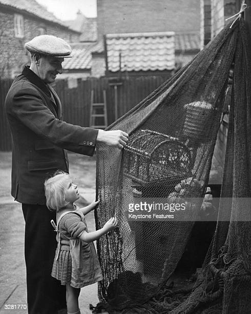 Three year old Dorothy helps her grandfather bowman W T Davies of the Cromer lifeboat with a shrimp net