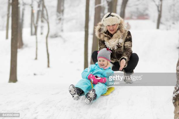 A three year old girl is on a sled