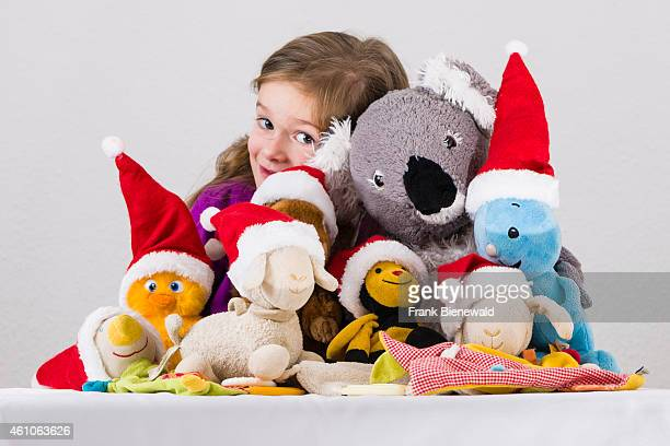 A three year old girl is presenting her favoured colorful cuddly toys wearing Santa Claus hats on a white table