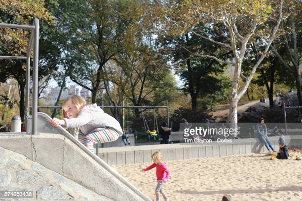 A three year old girl playing on a slide in a children's playground in Central Park Manhattan New York 4th November 2017