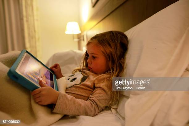 A three year old girl playing on an iPad in a hotel room during her vacation San Gimignano Tuscany Italy 25th October 2017 Photo by Tim...