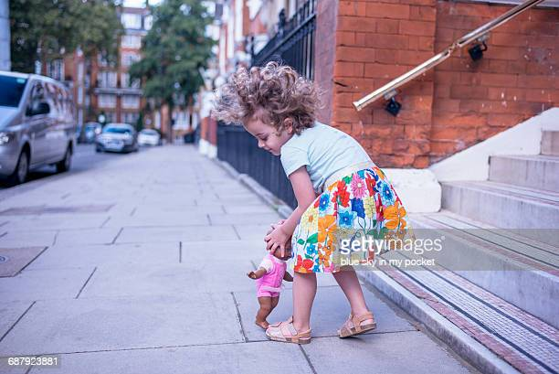 A three year old girl playing on the street.