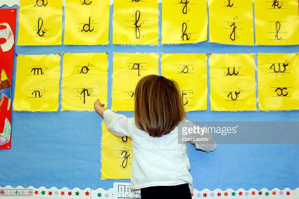 Three year old girl pointing at cursive letters