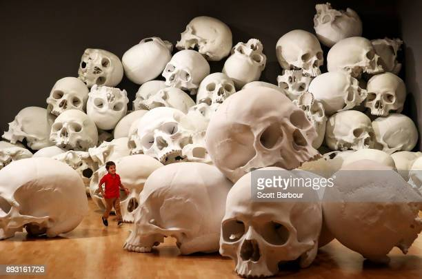 Three year old Josh Bedford runs through artist Ron Mueck's worldpremiere installation 'Mass' consisting of 100 largerthanlife skulls each measuring...