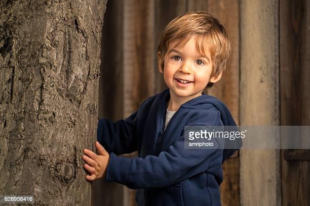 three year old kid that is peering behind a tree