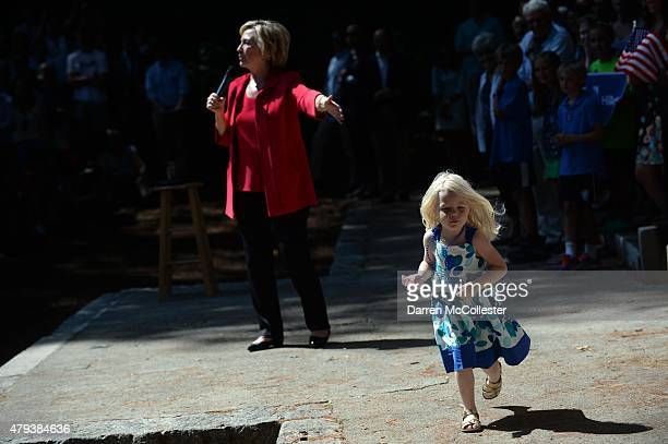 Three year old Louisa Hill runs across the stage as Democratic Presidential candidate Hillary Clinton speaks during a grassroots organizing event in...