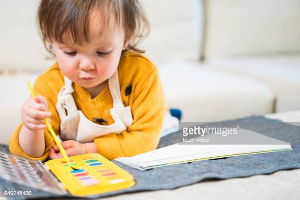 Three year old toddler painting a picture at home