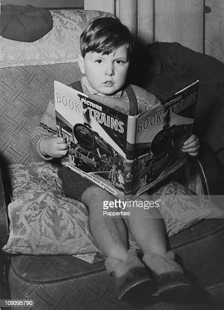 Three yearold Christopher Meaden with a picture book of trans at his home in Bethnal Green London 30th December 1961 Meaden has recently been...