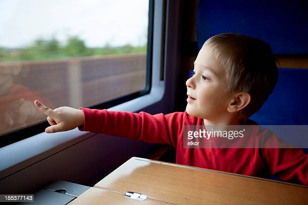 three years old boy travelling in train pointing at window - 4 5 years photos stock pictures, royalty-free photos & images