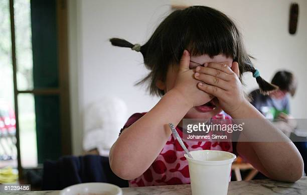 Three years old Cecilia covers her face during supper on May 26 2008 in Munich Germany Unicef United Nation's Children's Fund reports an alarming...