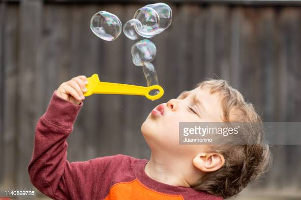 three years old child boy blowing bubbles - 2 3 years stock pictures, royalty-free photos & images