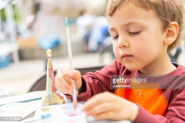 three years old child boy painting a clay figurine - 2 3 years stock pictures, royalty-free photos & images