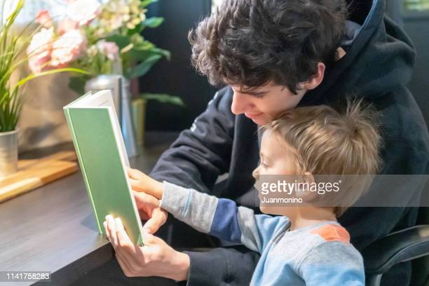 three years old child boy reading a book with his dad - 2 3 years stock pictures, royalty-free photos & images