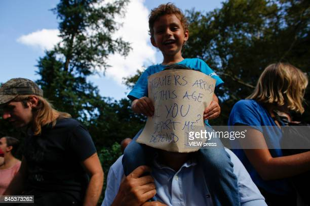 A three years old Child covers his father's face as he holds a placard during a march in protest of President Trump's decision on DACA in front of a...
