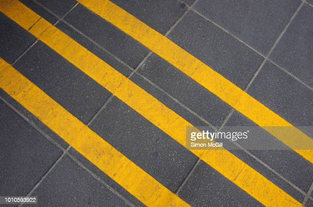 three yellow cycling 'rumble strips' lines on a footpath in melbourne to encourage cyclists to keep to the 10 kilometre per hour speed limit in the shared zone, victoria, australia - parallel stock pictures, royalty-free photos & images