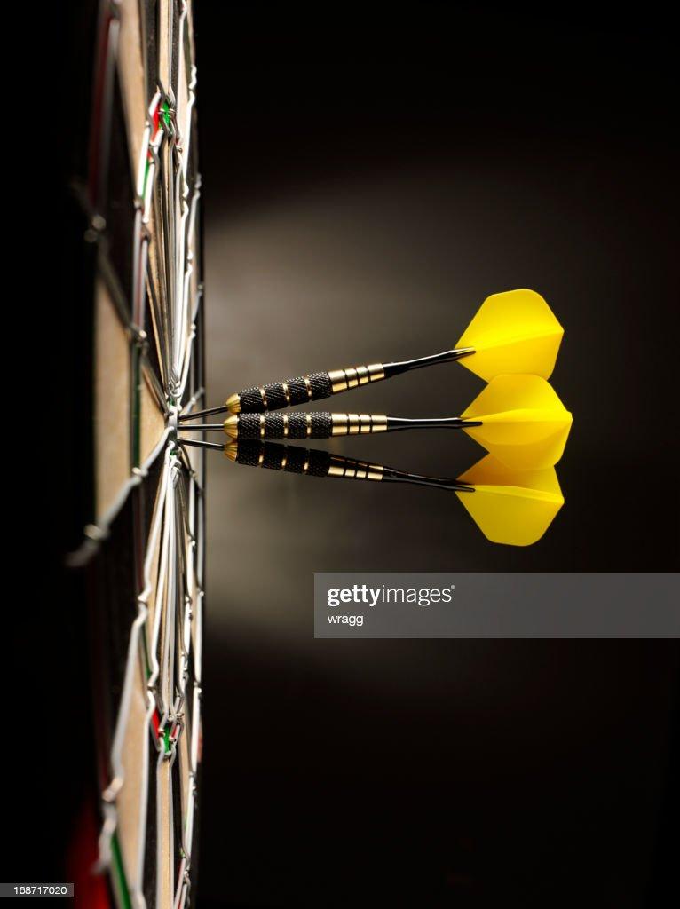 Three Yellow Darts in a Dartboard : Stock Photo