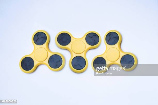 Three yellow fidget spinner stress relieving toy on white background