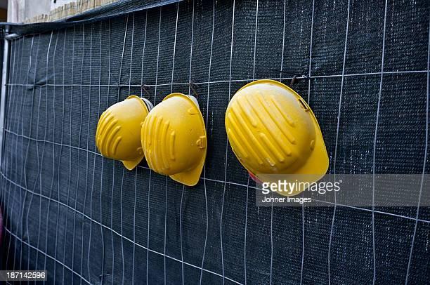 Three yellow hardhats hanging